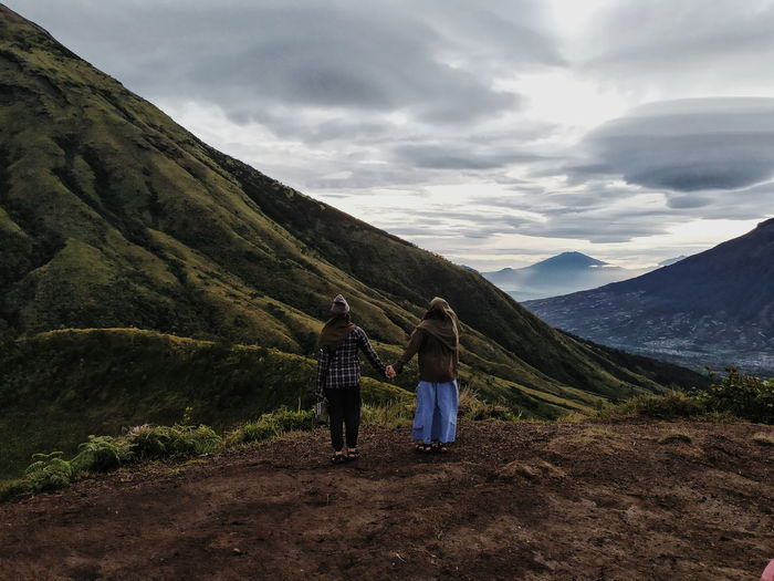 Rear view of people walking on mountain road against sky