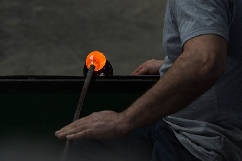 Midsection Of Man Making Glass In Factory