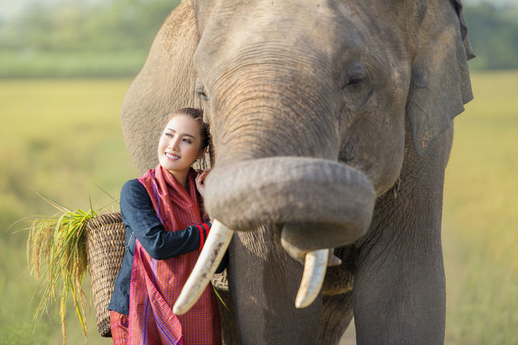 Smiling woman standing by elephant