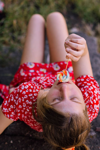 High angle view of woman eating lollipop while sitting outdoors