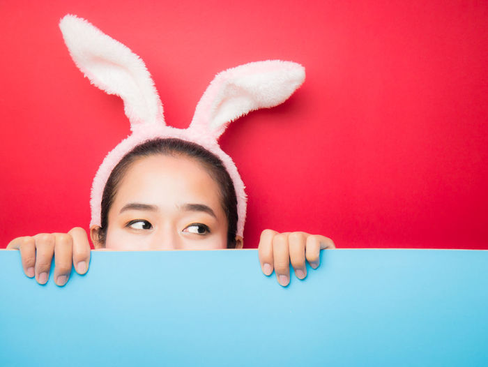Close-up of woman wearing rabbit ears while hiding behind blue cardboard
