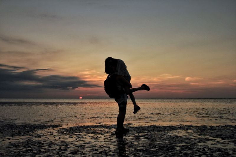 Man Lifting Woman On Wet Shore At Beach Against Sky During Sunset