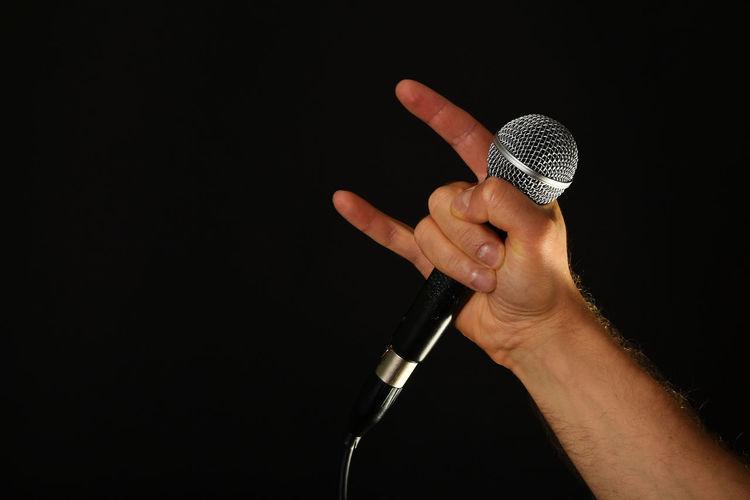 Male hand holding microphone with devil horns rock metal sign isolated on black background Blackandwhite Close-up Devil Frontman Girl Heaven Horn Human Hand Icon Metal Mi Microphone Music Nan Performance Radio Rock Rock'n'Roll Rocks Singer  Starbucks Studio Studio Shot Tv Vocalist