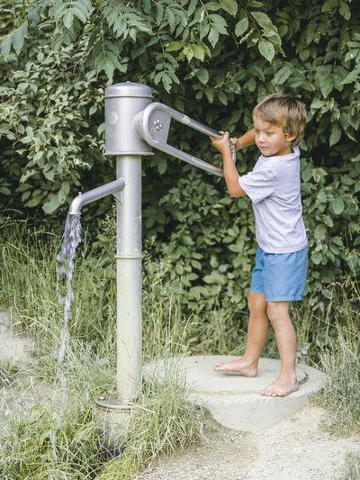 Full length of boy using water pump against plants
