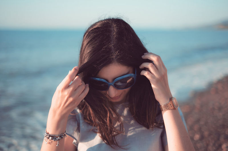 Portrait of young woman wearing sunglasses at beach