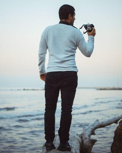 Rear view of man photographing at beach