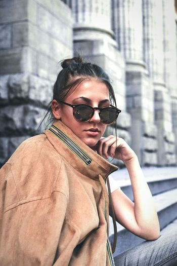 Portrait Of Woman Wearing Sunglasses Sitting Against Wall In City