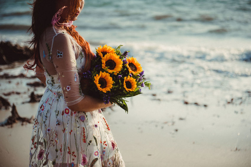 Beach Beauty In Nature Bouquet Bride Close-up Day Flower Flower Head Focus On Foreground Freshness Leisure Activity Lifestyles Midsection Nature One Person Outdoors Real People Rear View Sea Standing Wearing Flowers Women Yellow Young Adult Young Women