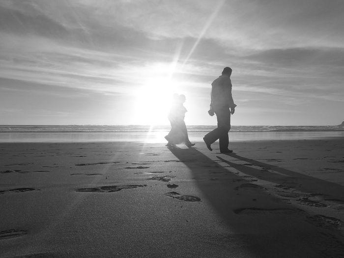 People Walking At Beach During Sunset
