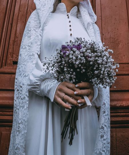 Midsection of bride holding flower