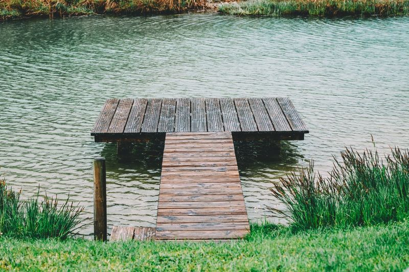 Built structure on field by lake