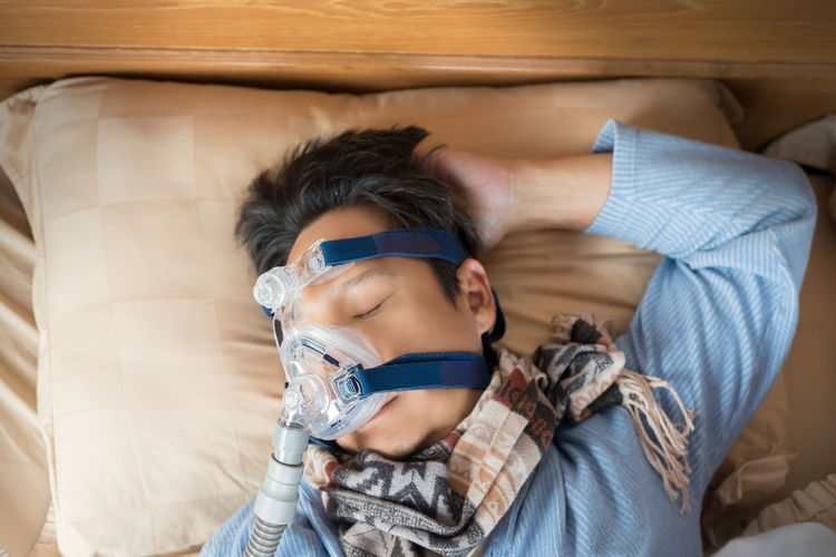 High angle view of mature man wearing oxygen mask while sleeping on bed