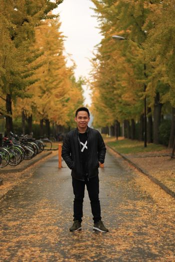 In the middle EyeEm Selects One Person Tree Looking At Camera Plant Full Length Redefining Menswear Portrait Real People Young Adult Front View Transportation Nature Men Young Men Lifestyles Standing Street Males  The Way Forward Autumn Outdoors