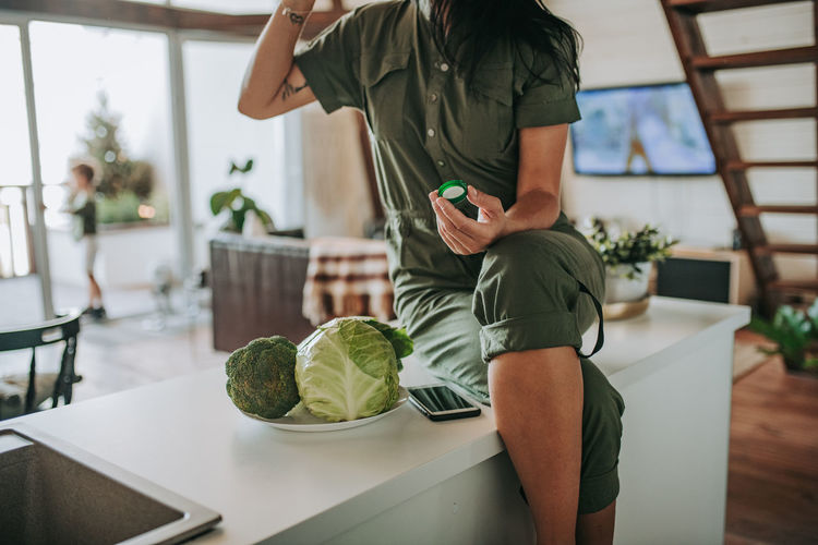 Midsection of woman standing on table