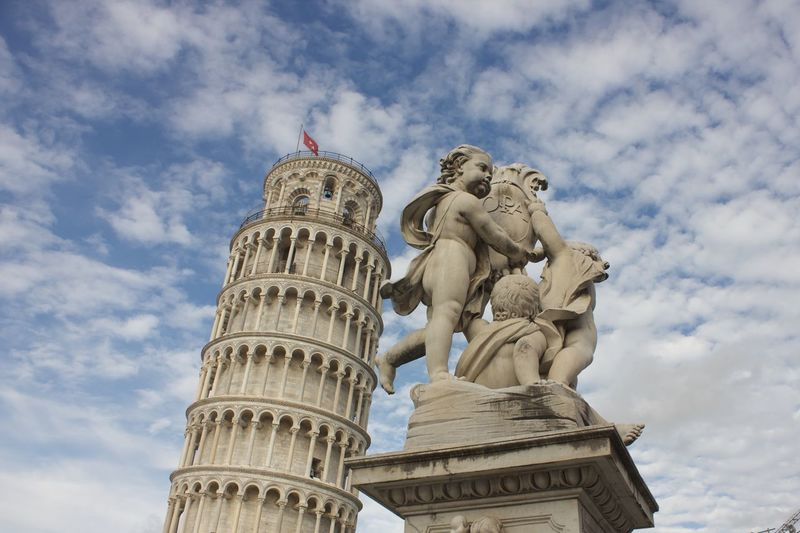 leaning tower of pisa and cherub statue Angel Architecture Art And Craft Building Exterior Built Structure Cloud - Sky Creativity Day History Human Representation Leaning Tower Of Pisa Low Angle View Male Likeness Nature No People Religion Representation Sculpture Sky Statue The Past Travel Destinations