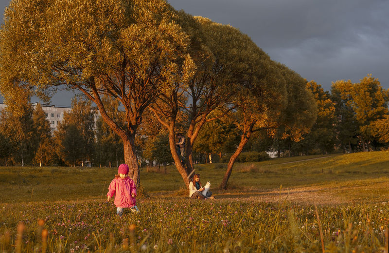 People on field by trees against sky during autumn