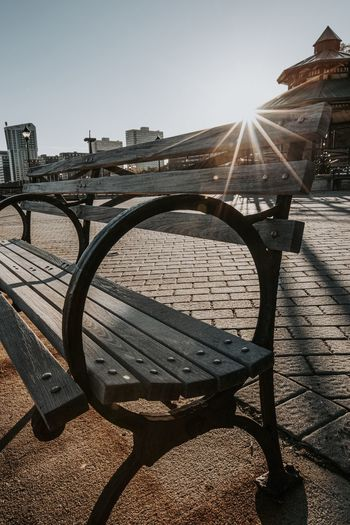 Empty bench against clear sky on sunny day