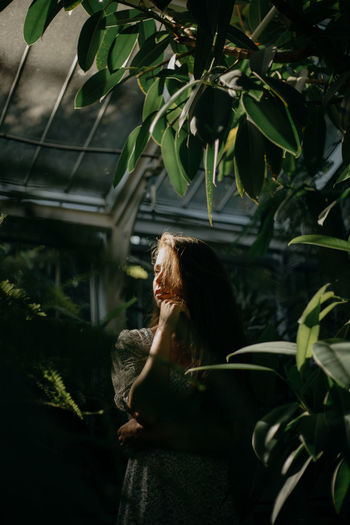 Portrait of a young woman amidst plants during sunset
