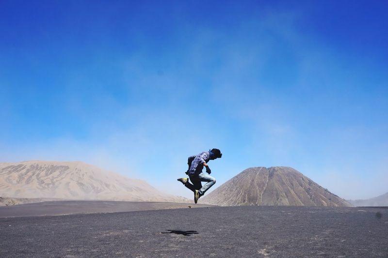 Man on arid landscape against sky