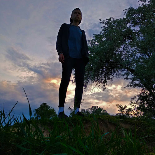 Low angle view of man standing against sky during sunset
