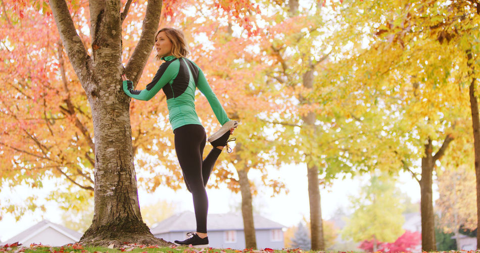 Autumn Balance Branch Day Exercising Flexibility Full Length Healthy Lifestyle Leaf Leisure Activity Lifestyles Low Angle View Motion Nature One Person One Woman Only One Young Woman Only Only Women Outdoors Park - Man Made Space Sports Clothing Tree Tree Trunk Young Adult Young Women