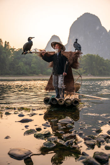 Senior man wearing hat standing on raft against mountain and sky