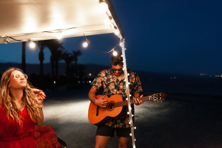 Man playing guitar for friend by illuminated campervan at night