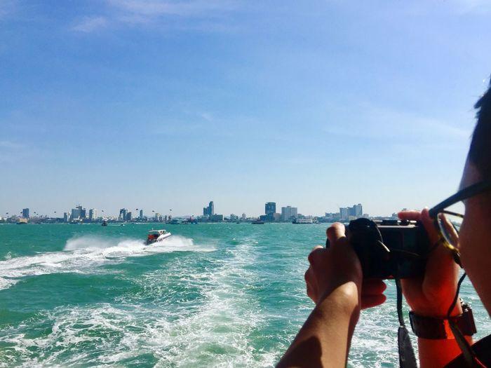 Man holding camera against sea