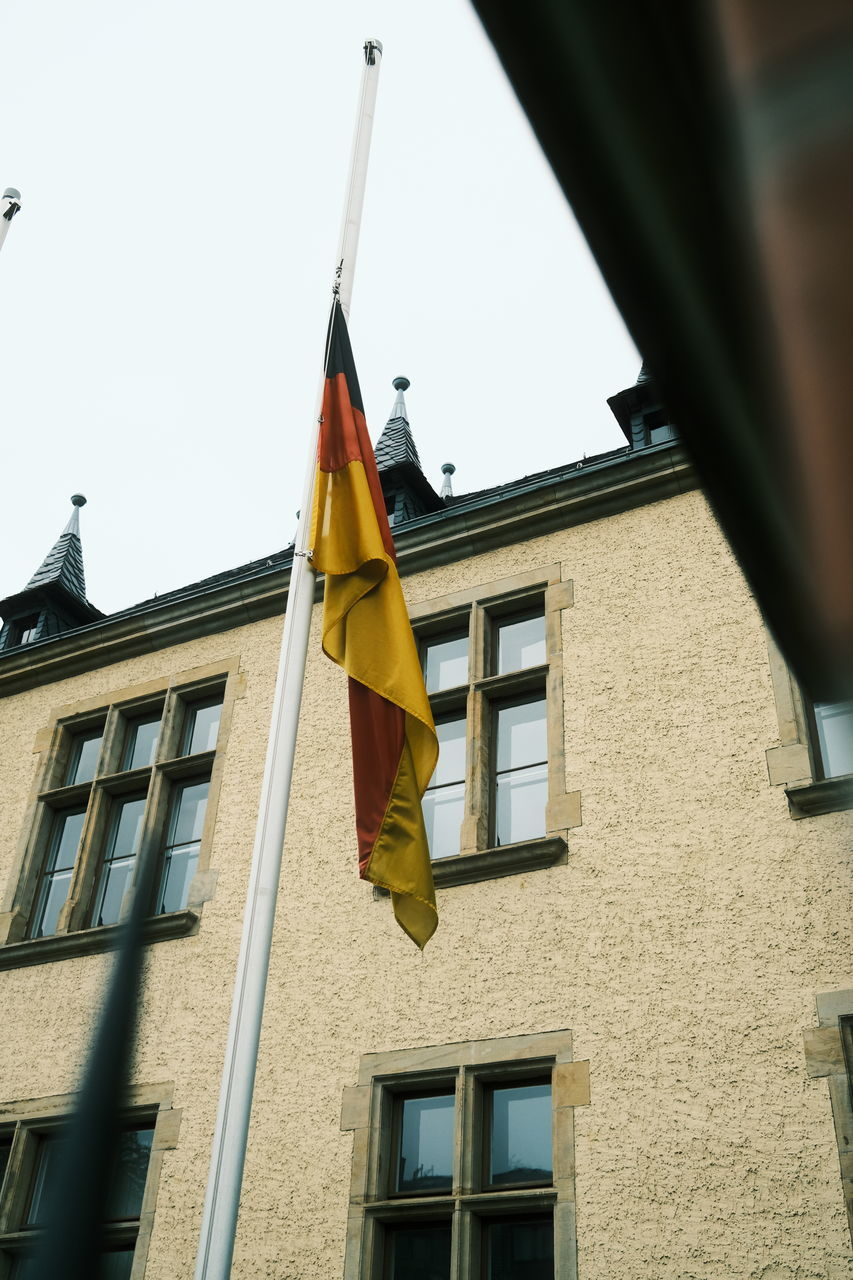 LOW ANGLE VIEW OF FLAG AGAINST BUILDINGS