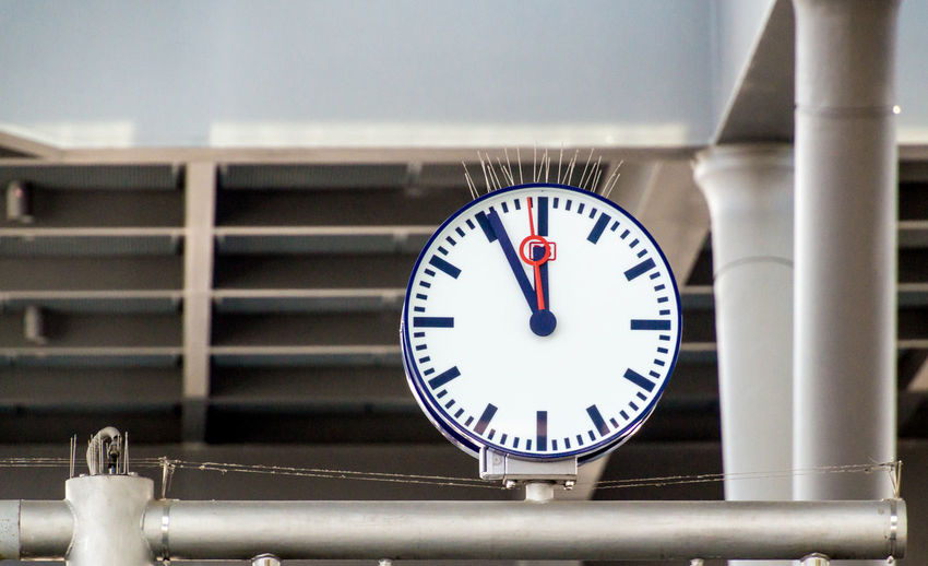Low angle view of clock on metal