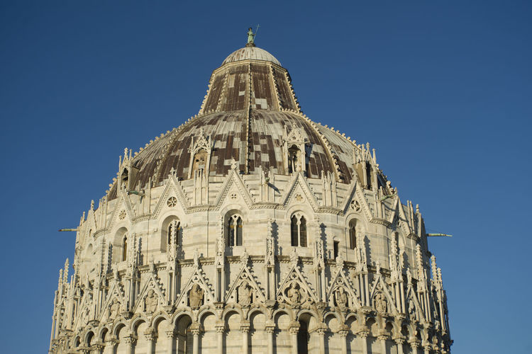 Low angle view of pisa baptistery against clear blue sky in city