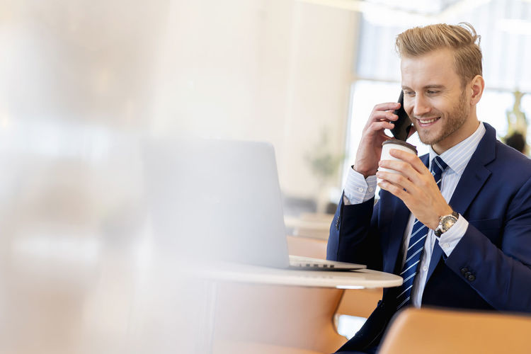 Businessman talking on phone at cafe