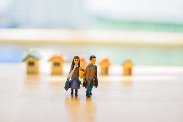 Close-Up Of Figurines And Model Homes On Table