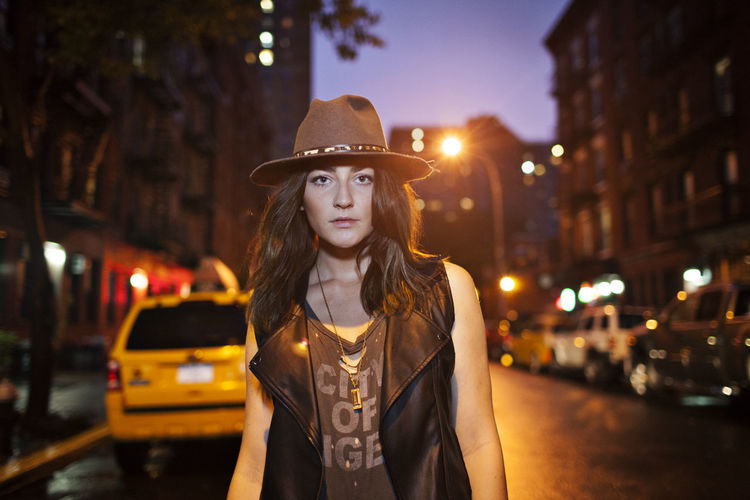 Portrait of beautiful woman standing on street in city at night