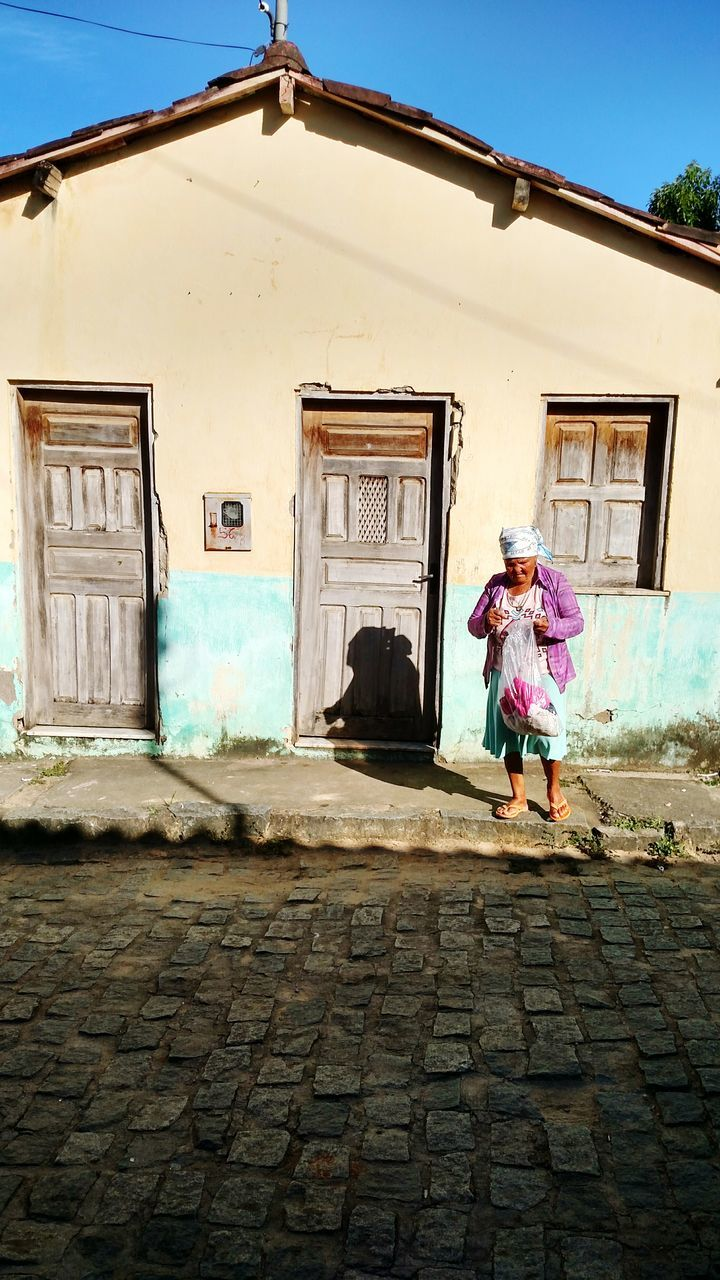 architecture, building exterior, built structure, full length, one person, building, real people, women, lifestyles, day, cobblestone, leisure activity, standing, street, walking, house, adult, casual clothing, outdoors