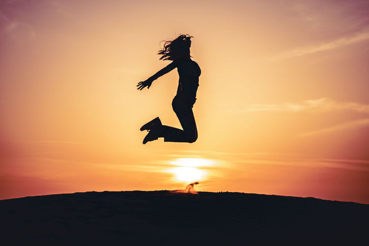 Silhouette woman jumping against orange sky during sunset