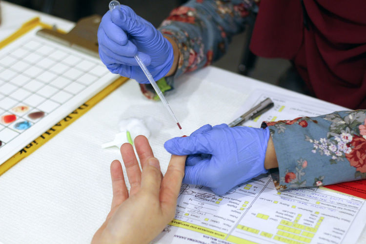 Cropped hands of doctor removing blood sample from patient finger