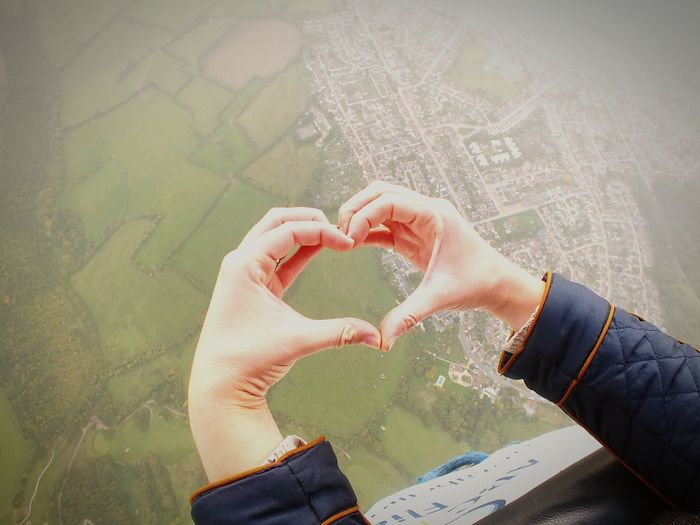 Person Making Heart Shape With Hands Against Residential District
