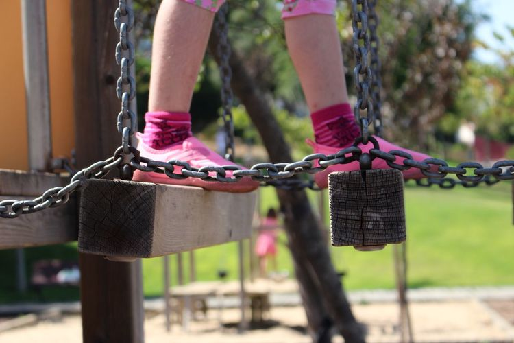 Low section of girl walking on balance beam at playground