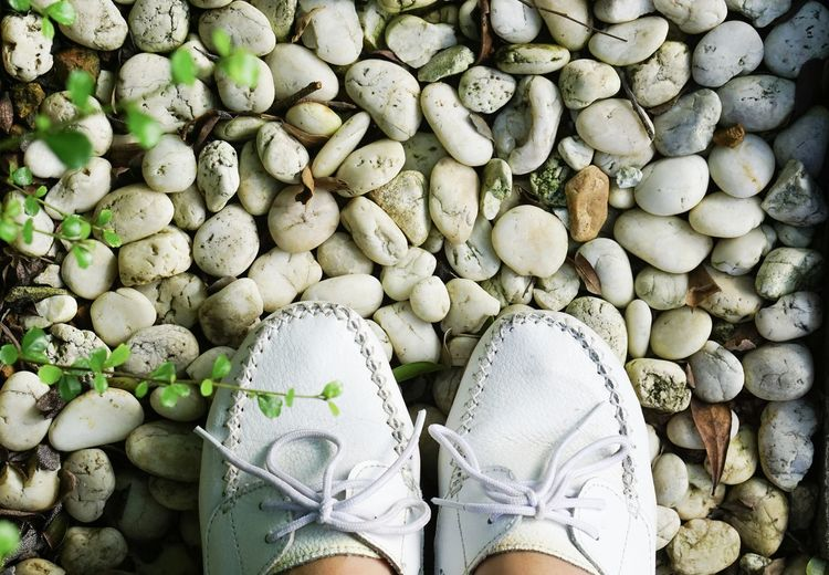 Low section of person wearing white shoes standing on pebbles