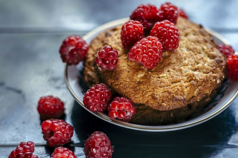 Close-up of raspberries with cookies on table