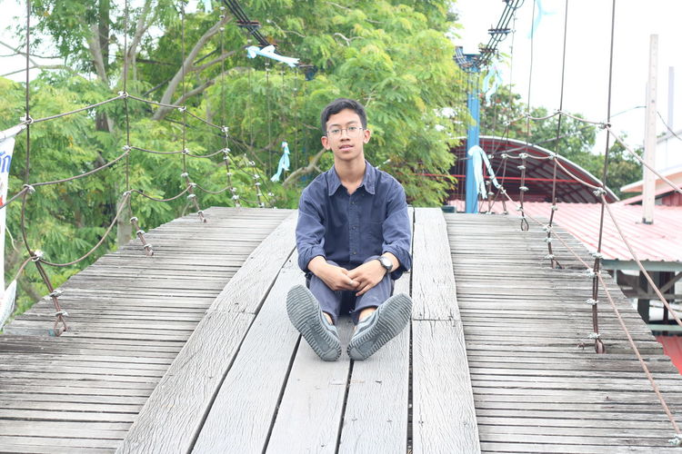 Portrait of young man sitting on footbridge