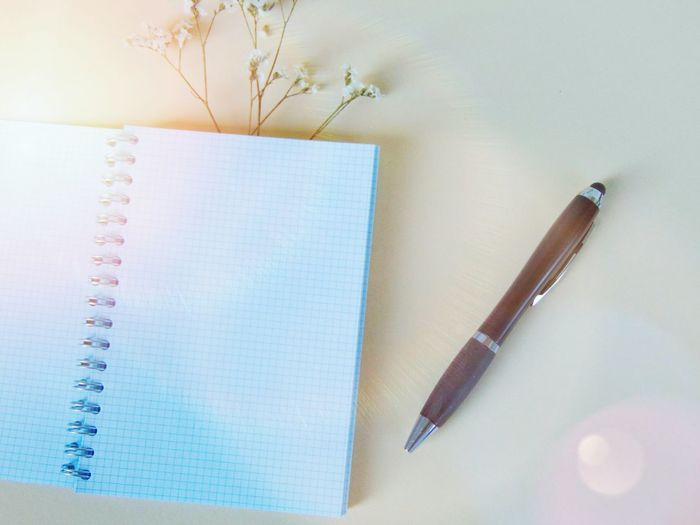 High angle view of pen and blank diary with flower on colored background