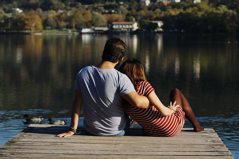 Rear view of couple sitting on pier over lake