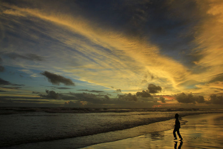 Yogyakarta-Indonesia, 18/04/2018: Silhouette boys play on the Parangtritis beach alone at dusk with dramatic sunset sky. Sky Cloud - Sky Sunset Water Sea Beach Beauty In Nature Land One Person Lifestyles Scenics - Nature Silhouette Real People Horizon Over Water Full Length Orange Color Nature Walking Leisure Activity Outdoors Sunset Silhouettes Sunset #sun #clouds #skylovers #sky #nature #beautifulinnature #naturalbeauty #photography #landscape Seascape Ocean View Waves, Ocean, Nature Dramatic Sky