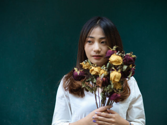Young woman holding flower bouquet standing against colored background