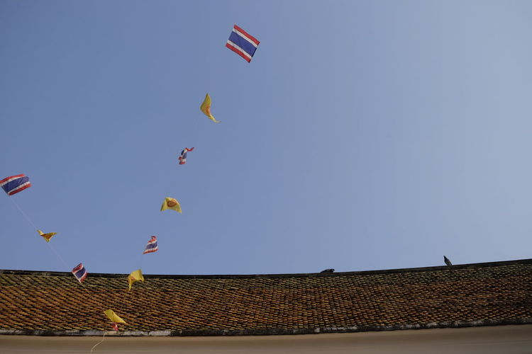 Low angle view of flags hanging from house roof against sky
