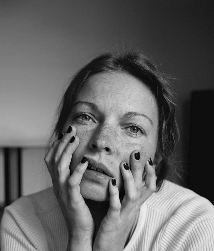 Close-up portrait of woman with hands on chin at home