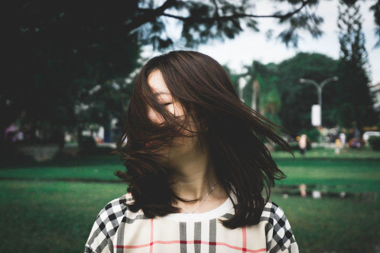 Young woman shaking head while standing at park