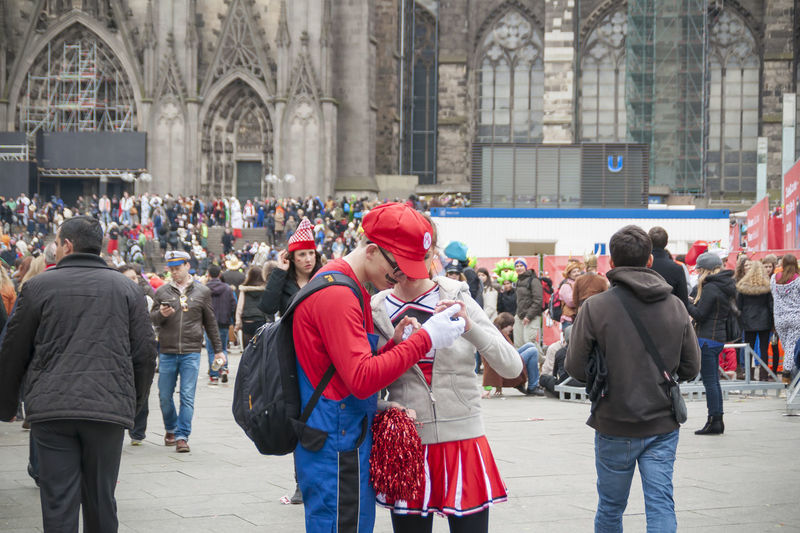 Cologne, Germany – March 14th 2014: in front of Cologne Cathedral is a large group of unknown people Carnival Celebration Cologne Disguise Domplatte Downtown Lifestyle Many People Mario Brother Rose Monday Cell Phone  Chearleader City Cologne Cathedral Costume Day Dress Up Group Of Unknown People Large Group Of People Leisure Activity Party People Real People Street Street Carnival Young Man